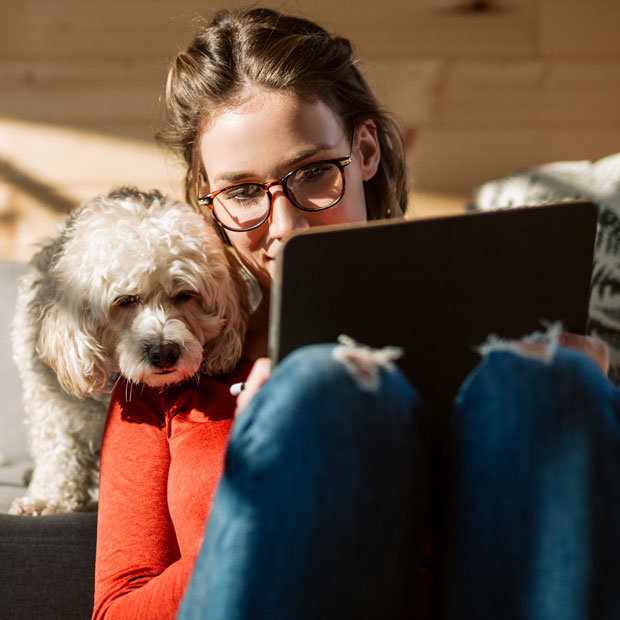 Woman on laptop with white dog looking over her shoulder