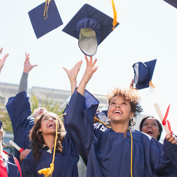 Graduating students throw mortarboards into the air